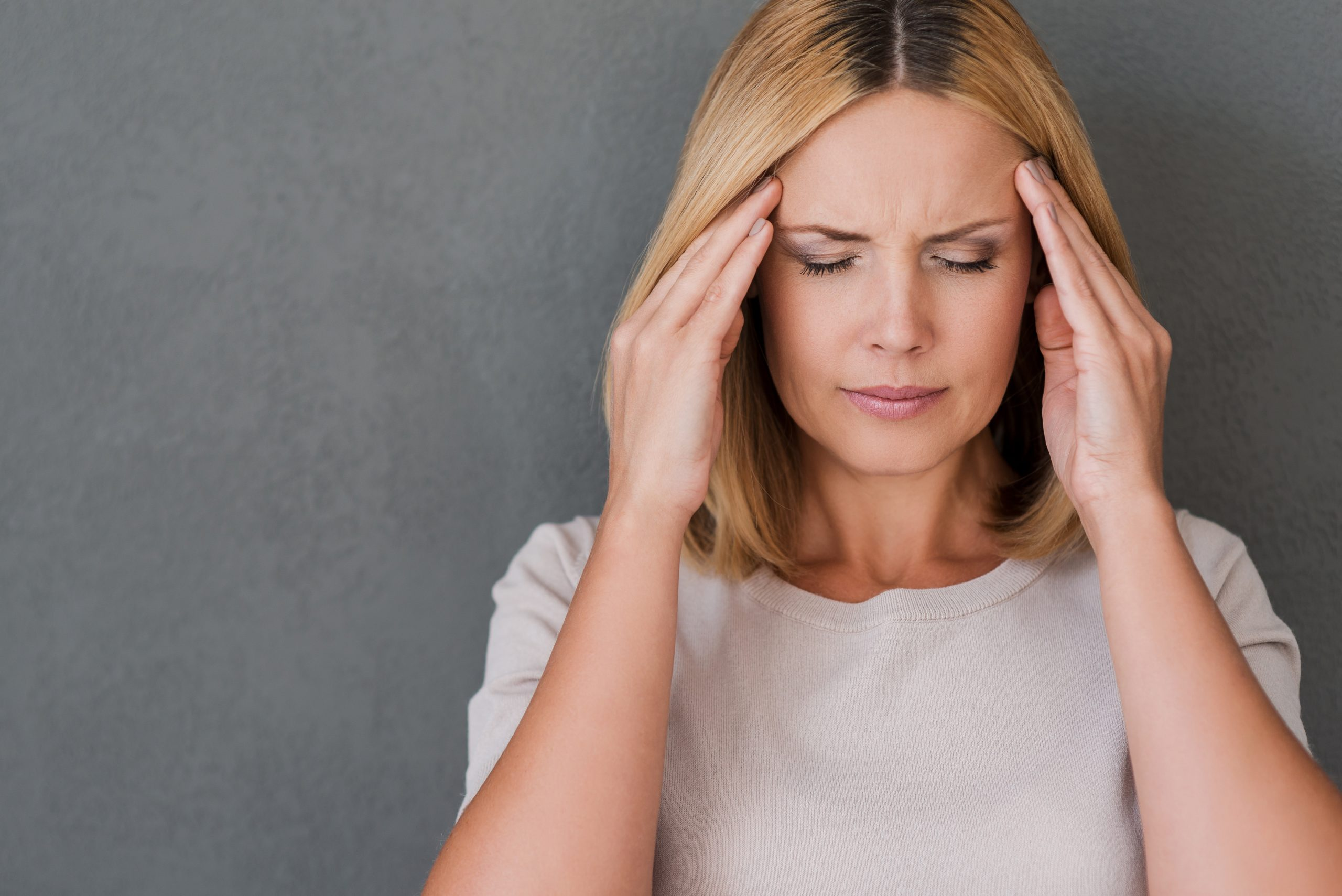 I need some painkillers. Depressed mature woman touching forehead and keeping eyes closed while standing against grey background