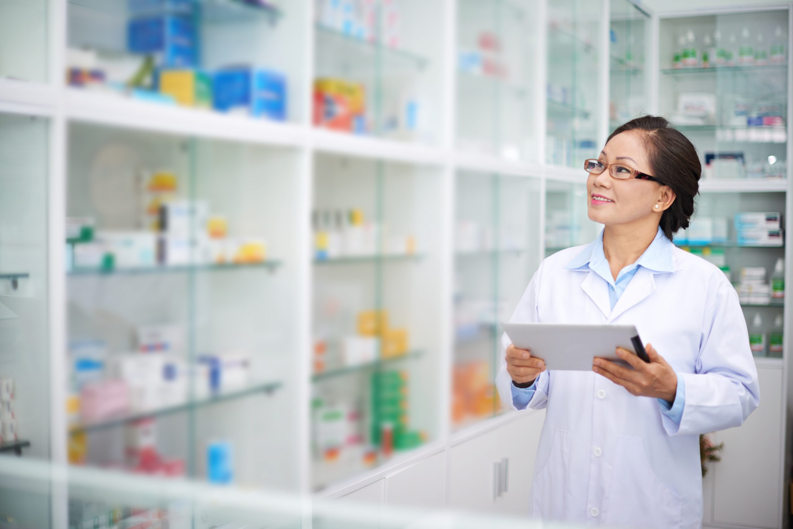 Asian pharmacist with digital tablet working in drugstore